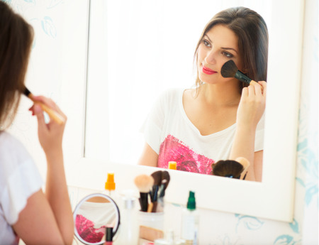 Beautiful girl looking in the mirror and applying cosmetic photo