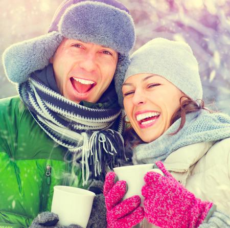 niñas sonriendo: Pares felices del invierno divertirse al aire libre. Bebidas calientes