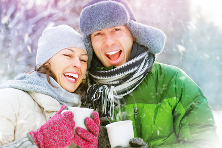 Happy winter couple having fun outdoors. Hot drinks photo