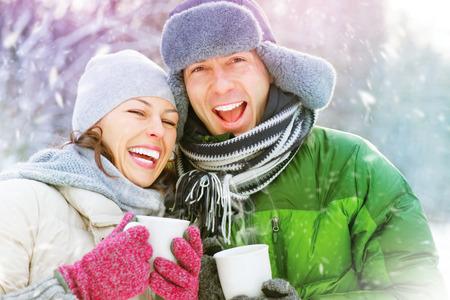 frio: Pares felices del invierno divertirse al aire libre. Bebidas calientes