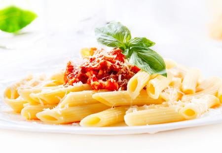 Penne pasta con salsa boloñesa, queso parmesano y albahaca Foto de archivo - 32267198