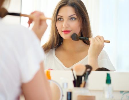 mujer maquillandose: Muchacha hermosa que mira en el espejo y que aplica el cosmético