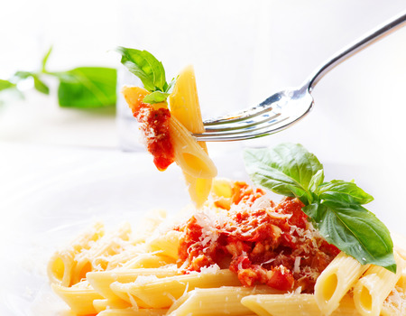 Penne pasta met bolognese saus, Parmezaanse kaas en basilicum Stockfoto