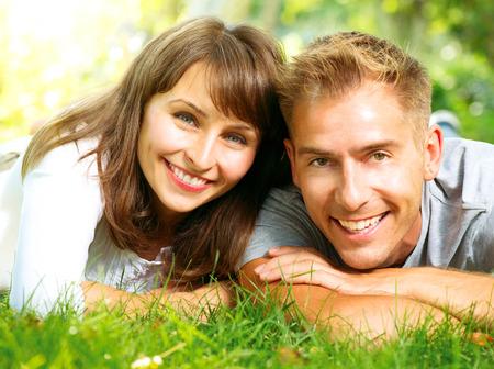 dientes sanos: Pareja sonriente feliz junto relajante en la hierba verde Foto de archivo