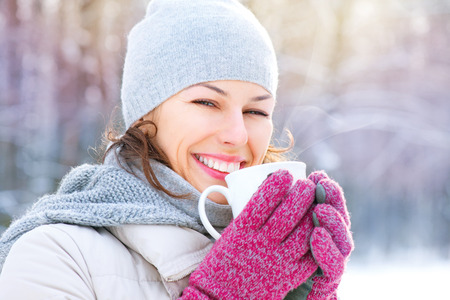 Beautiful happy smiling winter woman with hot drink photo