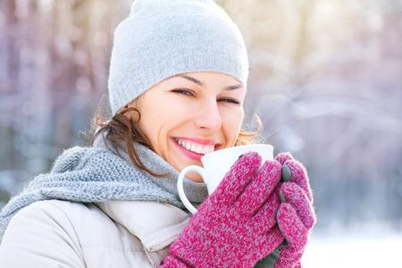 raffreddore: Bella donna sorridente felice in inverno con la bevanda calda