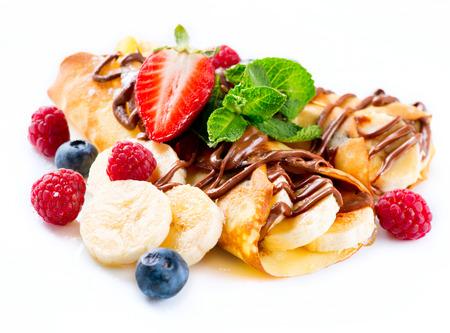 Pannenkoeken met banaan, chocolade en bessen over wit Stockfoto