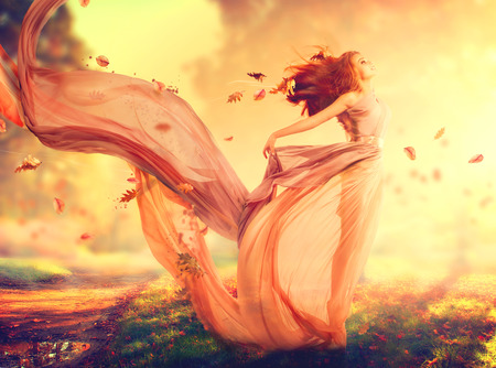 Autumn fantasy girl, fairy in blowing chiffon dress photo