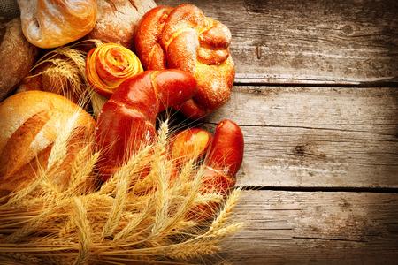 木製のテーブルのベーカリーのパン。パンと小麦の穂の束 写真素材