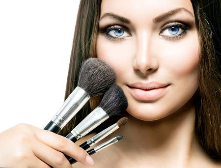 Schoonheid meisje met make-up kwasten. Het toepassen van make-up