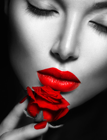 Beautiful sexy woman with red lips, nails and rose flower