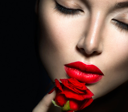 Beautiful woman with red lips, nails and rose flower