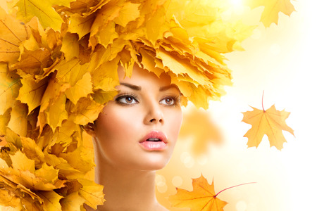 vẻ đẹp: Phụ nữ mùa thu với lá vàng kiểu tóc. Fall. Trang điểm sáng tạo