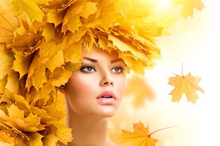 schoonheid: Vrouw van de herfst met gele bladeren kapsel. Vallen. Creatieve make-up Stockfoto