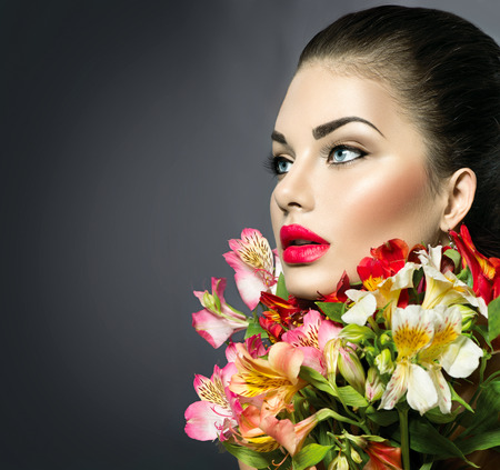 High fashion model girl with colorful flowers and red lips Stock Photo