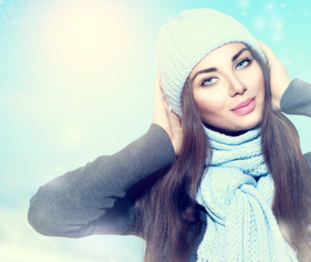 Beauty winter girl wearing hat and scarf photo