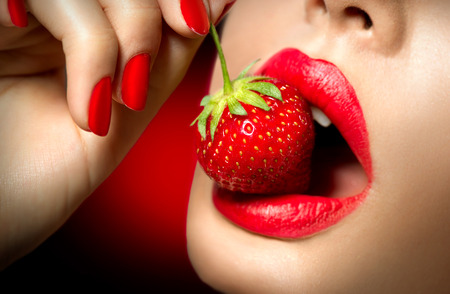 sensual nude: Sexy Woman Eating Strawberry. Sensual Red Lips Stock Photo