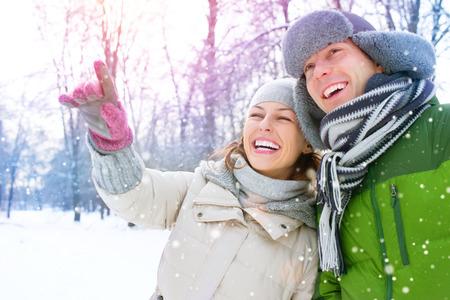 ropa invierno: Vacaciones de invierno. Pareja feliz divertirse al aire libre Foto de archivo