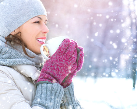 Belle sourire heureux hiver Femme avec boisson chaude en plein air