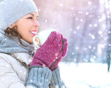 frio: Hermosa feliz sonriente del invierno Mujer con la bebida caliente al aire libre