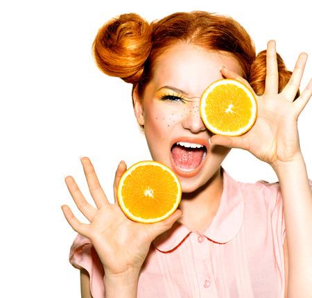 Chica adolescente alegre con el peinado rojo divertido. Naranjas jugosas