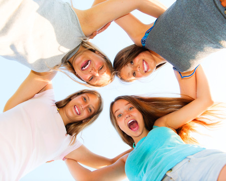 riendo: Grupo de amigos que sonríen permanecer juntos en el cielo azul