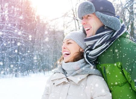 ropa de invierno: Vacaciones de invierno. Pareja feliz divertirse al aire libre Foto de archivo