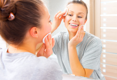 facial cleansing: Beauty teenage girl cleaning her face with cotton pad at home Stock Photo