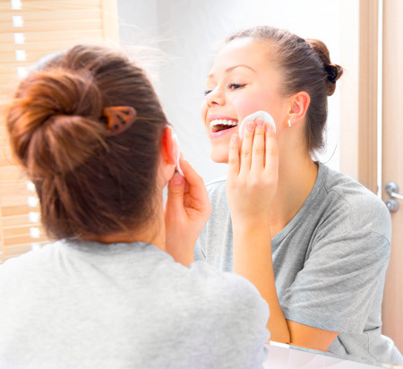 removing make up: Beauty teenage girl cleaning her face with cotton pad at home Stock Photo