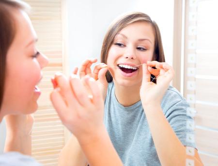 higiena: Uroda nastoletnia dziewczyna nitkowanie zębów w domu. Higiena jamy ustnej