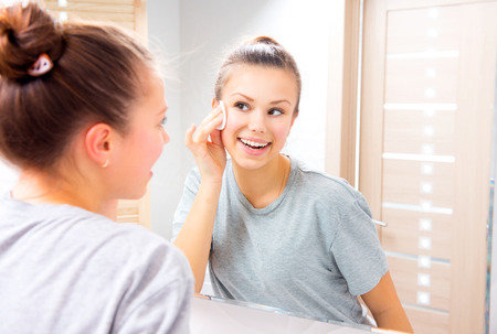 Beauty teenage girl cleaning her face with cotton pad at home Foto de archivo