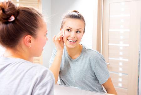 pulizia viso: Bellezza adolescente pulizia viso con un tampone di cotone a casa Archivio Fotografico