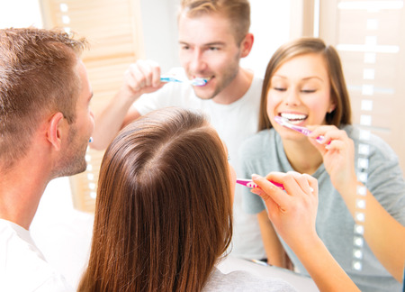 Young couple in the bathroom brushing teeth together photo