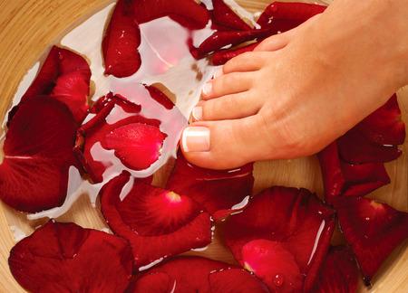 pedicura: Pies Spa. Pedicura. Piernas femeninas en agua con pétalos de rosa