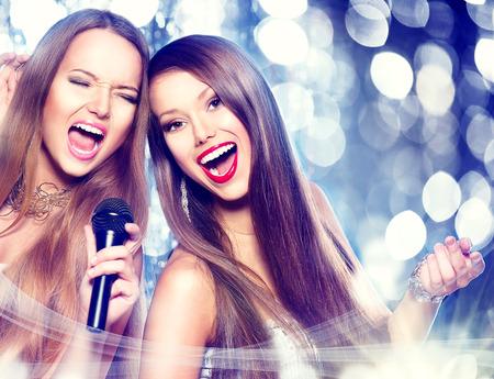 Karaoké. les filles de beauté avec un micro chant et la danse Banque d'images - 33475625