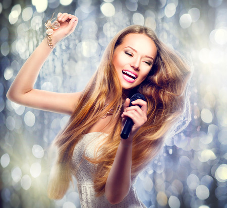 Beauty model girl with a microphone singing and dancing photo