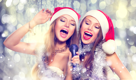 Christmas party, karaoke. Beauty girls in santa hats singing photo