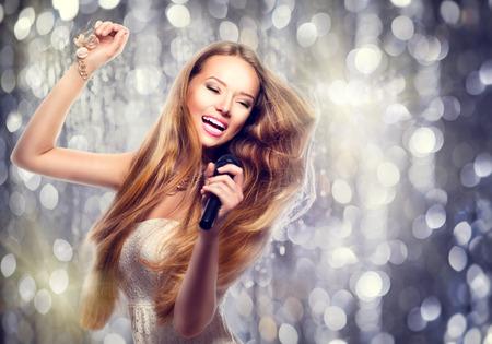 gente cantando: Belleza chica modelo con un micr�fono cantando y bailando Foto de archivo