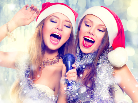 young people party: Christmas party, karaoke. Beauty girls in santa hats singing Stock Photo