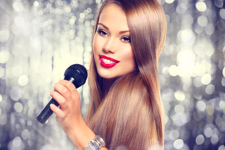 Singing woman. Beautiful girl singing over holiday background photo