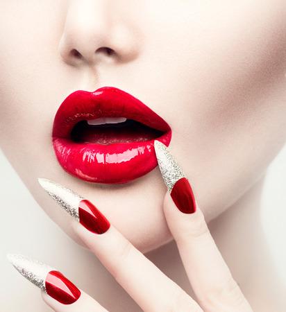 Make-up en manicure. Rode lange nagels en Red Glossy Lips Stockfoto