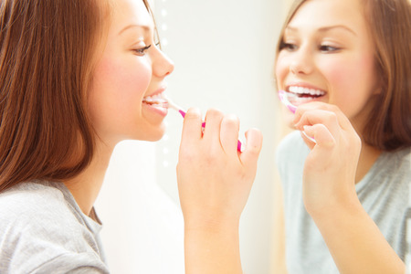 Pretty young woman brushing her teeth. Dental hygiene photo