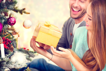Happy Couple with Christmas Gift at Home photo