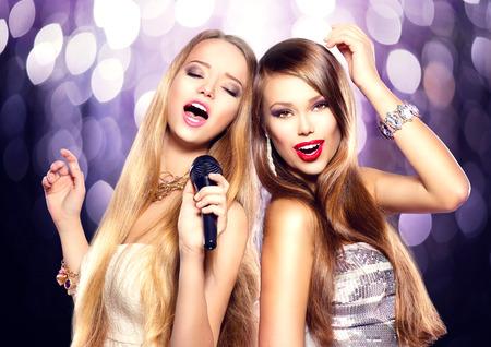 persona cantando: Karaoke. Muchachas de la belleza con un micrófono cantando y bailando
