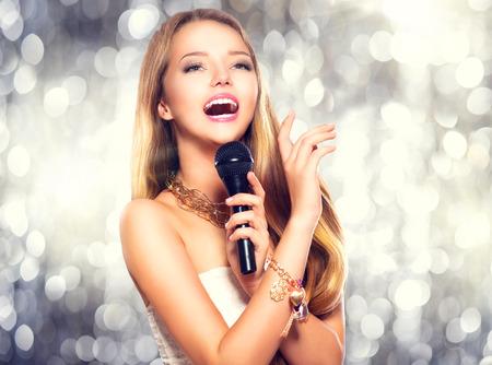 Model van de schoonheid meisje met een microfoon zingen en dansen Stockfoto