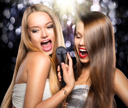 dancing club: Karaoke. Beauty girls with a microphone singing and dancing