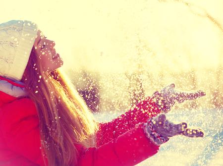 mood: Beauty winter girl blowing snow in frosty winter park