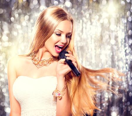 cantando: Belleza chica modelo con un micrófono cantando y bailando Foto de archivo