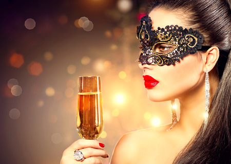 Sexy model vrouw, gekleed in carnaval masker met een glas champagne Stockfoto