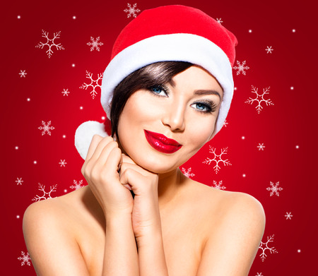 blue eyes: Christmas Woman. Beauty Model Girl in Santa Hat over Red Stock Photo
